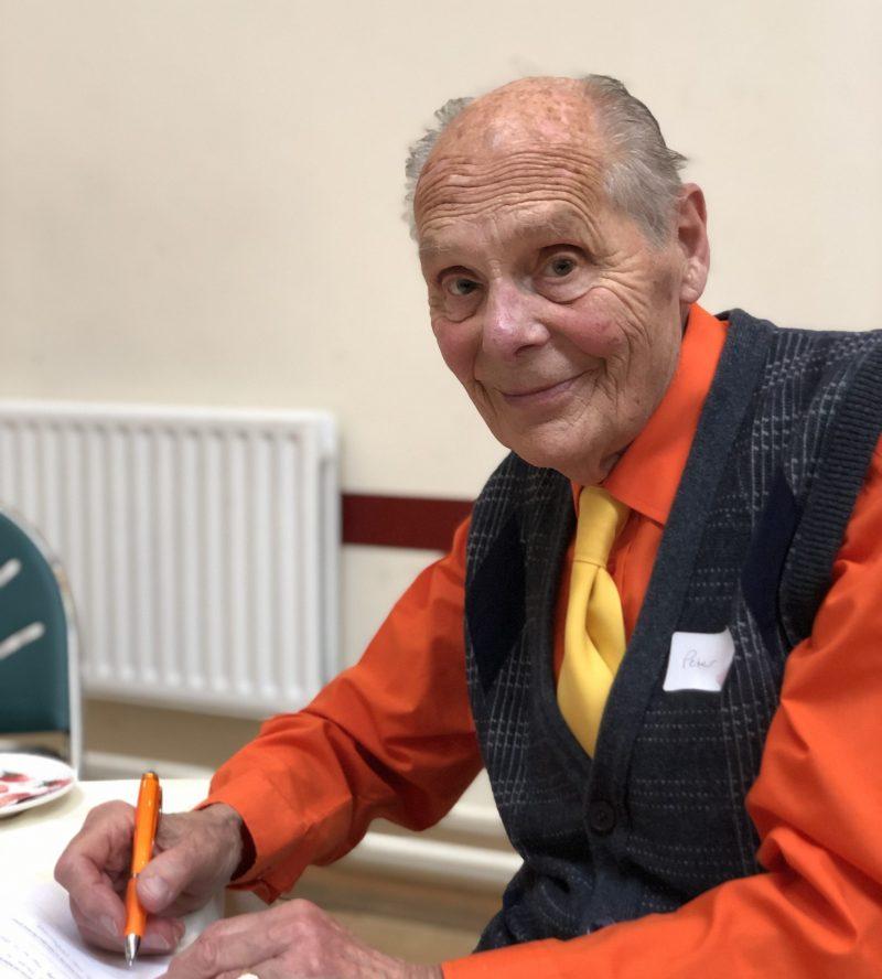 elderly man in orange shirt