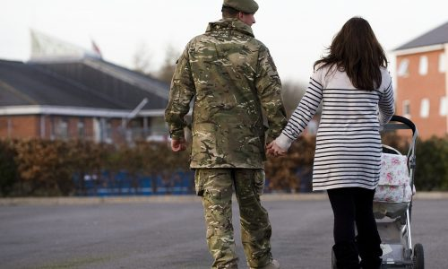 Male soldier holding hands with woman pushing pram