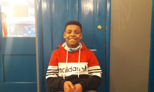 smiling boy against blue door