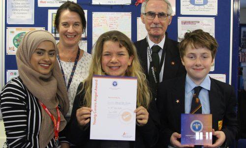 Children and teachers holding award