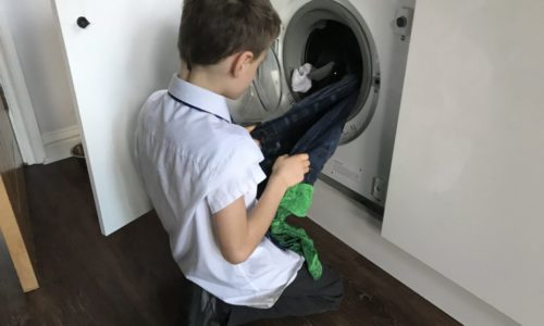 child emptying washing machine