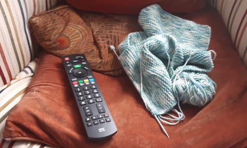 TV handset and knitting on chair