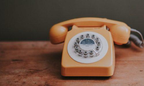 orange telephone on table