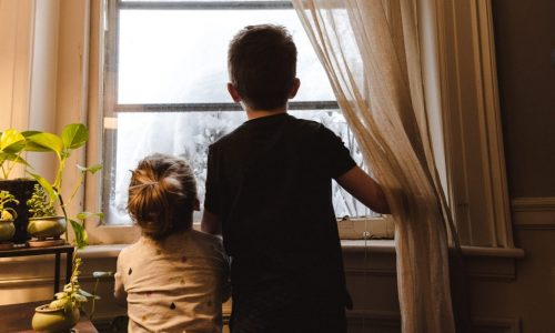 rear view of children looking out of window
