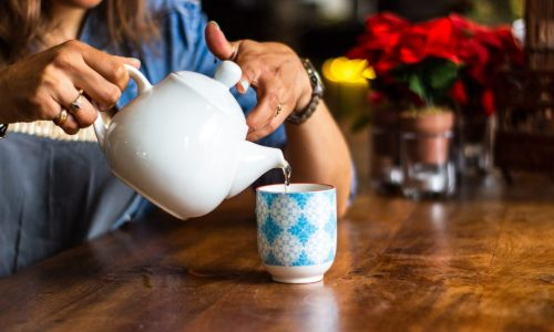 Woman's handspouring cup of tea