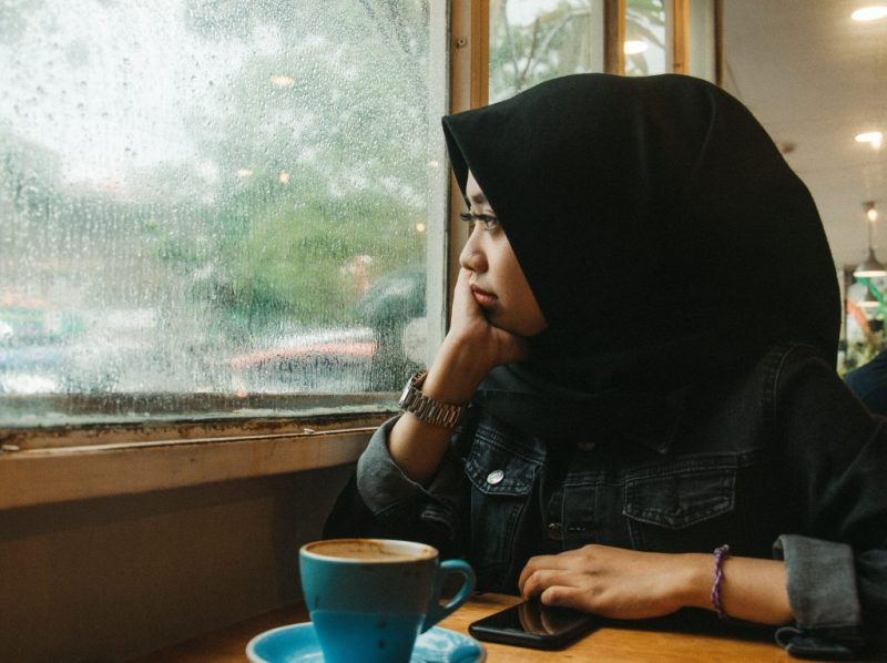 woman in headscarf looking out of window