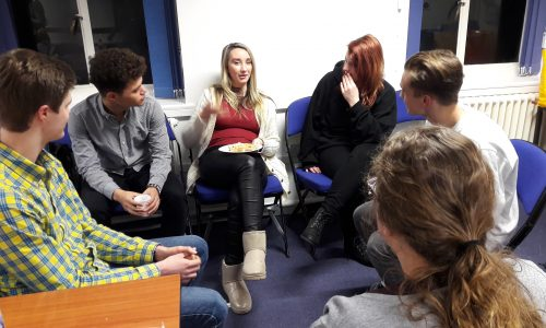 Young adults sitting in a room talking