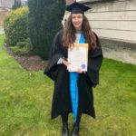 young woman in cap and gown holding degree certificate