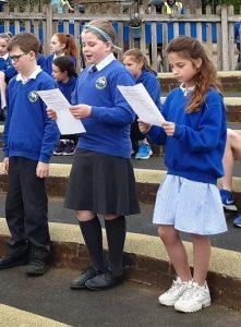 schoolchildren reading aloud at an outdoor assembly