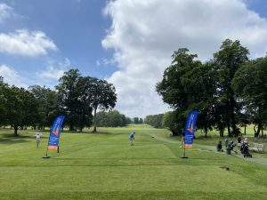golfers blaying between Aaction for Carers Surrey flags