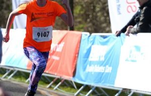 girl running in funrun in orange charity tshirt