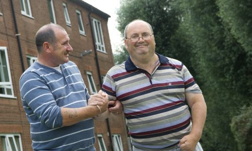Man and carer outdoors