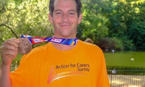 smiling man in orange tshirt with marathon medal